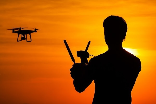 Man operating of flying drone quadrocopter at sunset light