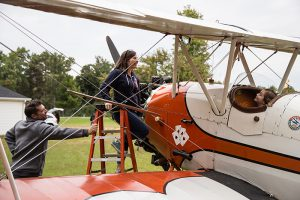 Filmmakers Adam & Kara White line up a shot with actress Katie Broecker in an authentic 1929 Travel Air